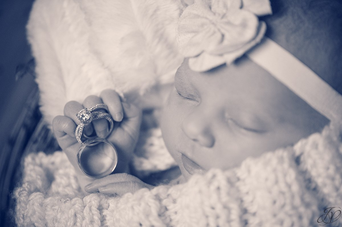 newborn holding parent's wedding rings
