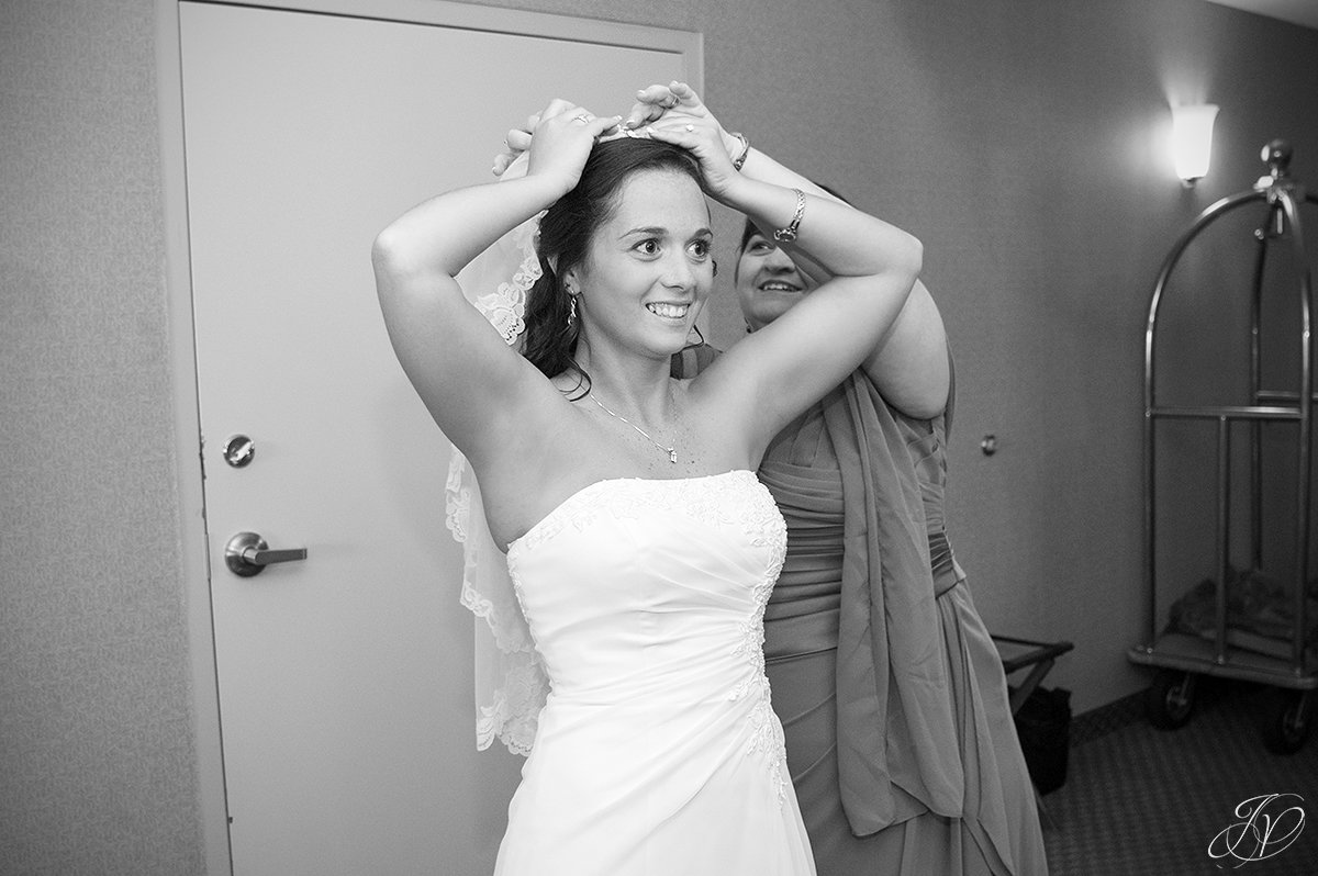 black and white photo of mom helping bride with veil