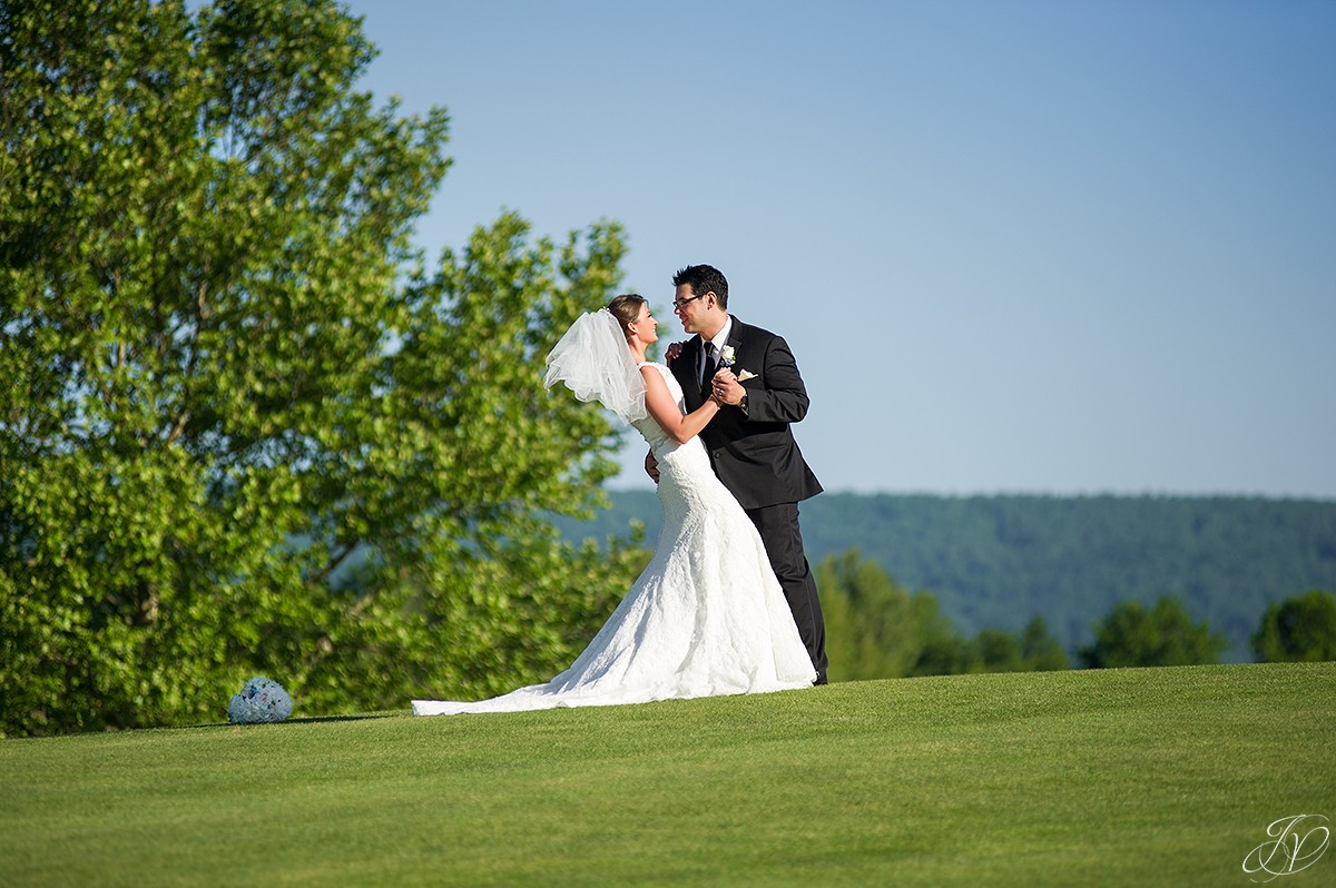 groom dipping bride outside on golf course