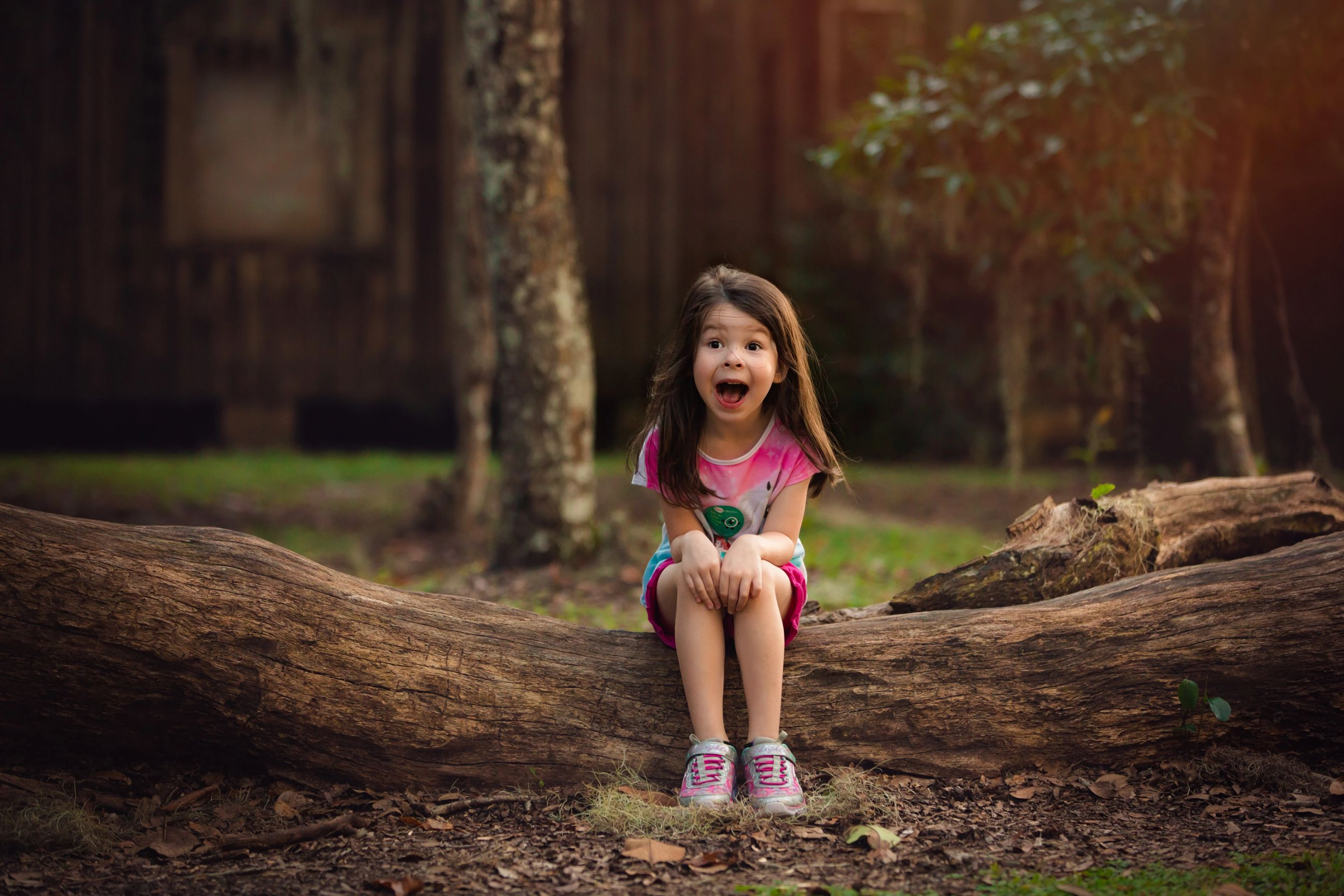 Cute little girl during a family portraits session with a huge smile and crazy hair by Alyssa Renee Photography