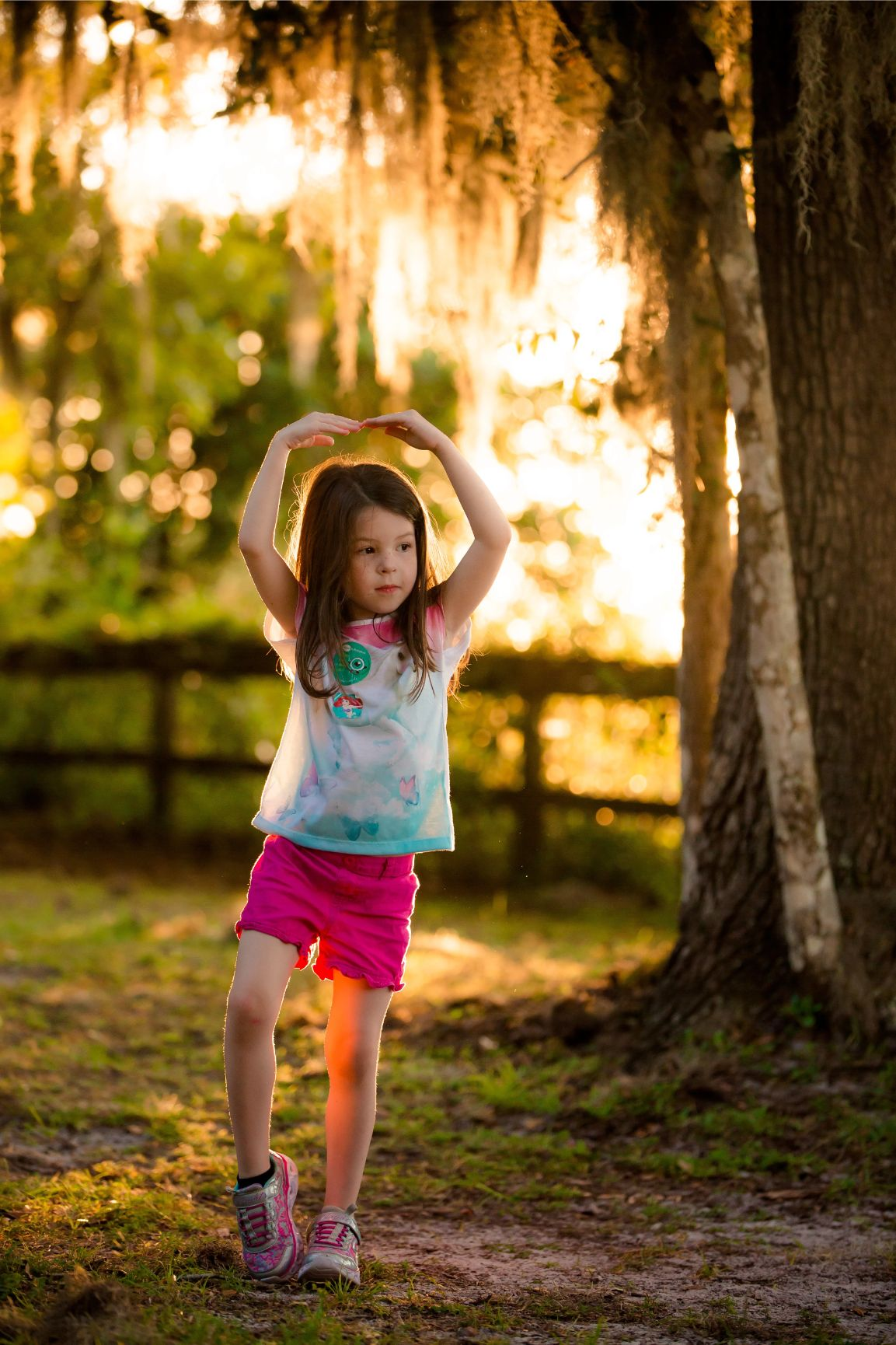 Child doing a dance pose during a portrait session at Alpine Groves Park at great place to take pictures