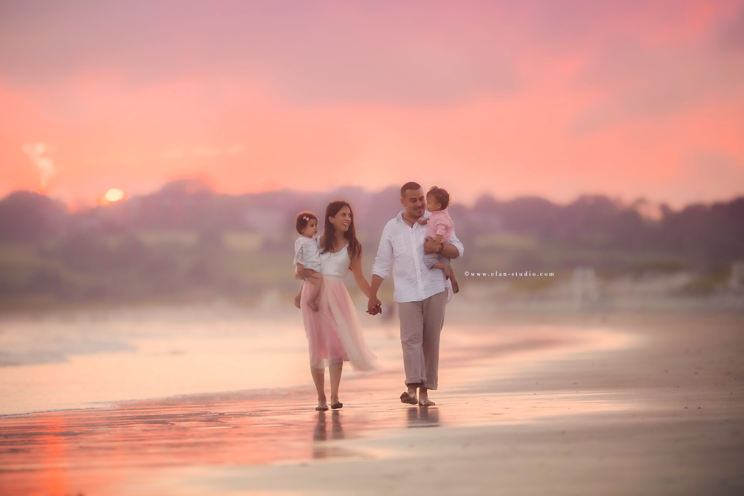 dreamy pink hued image of family walking on beach at sunset, by Elan Studio