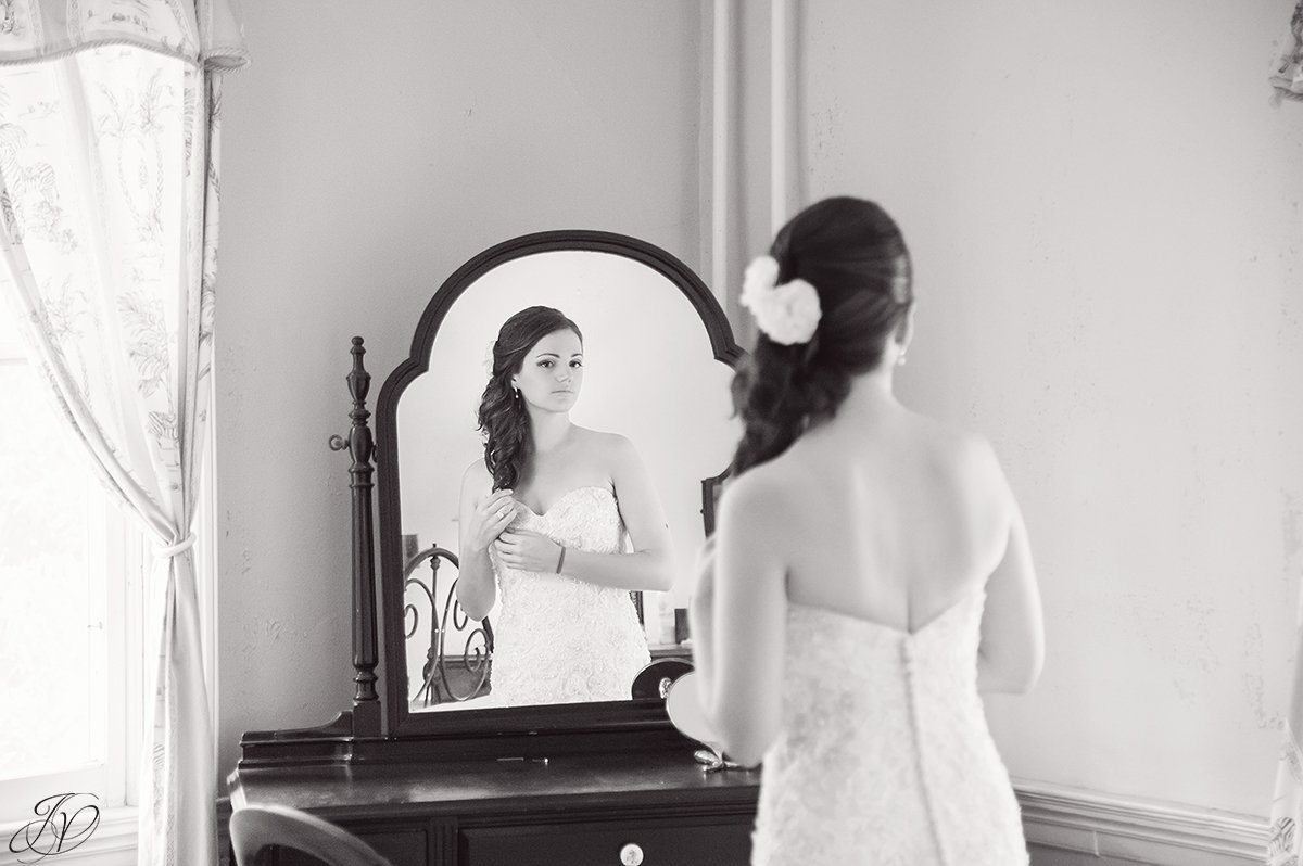 beautiful image of bride looking in mirror