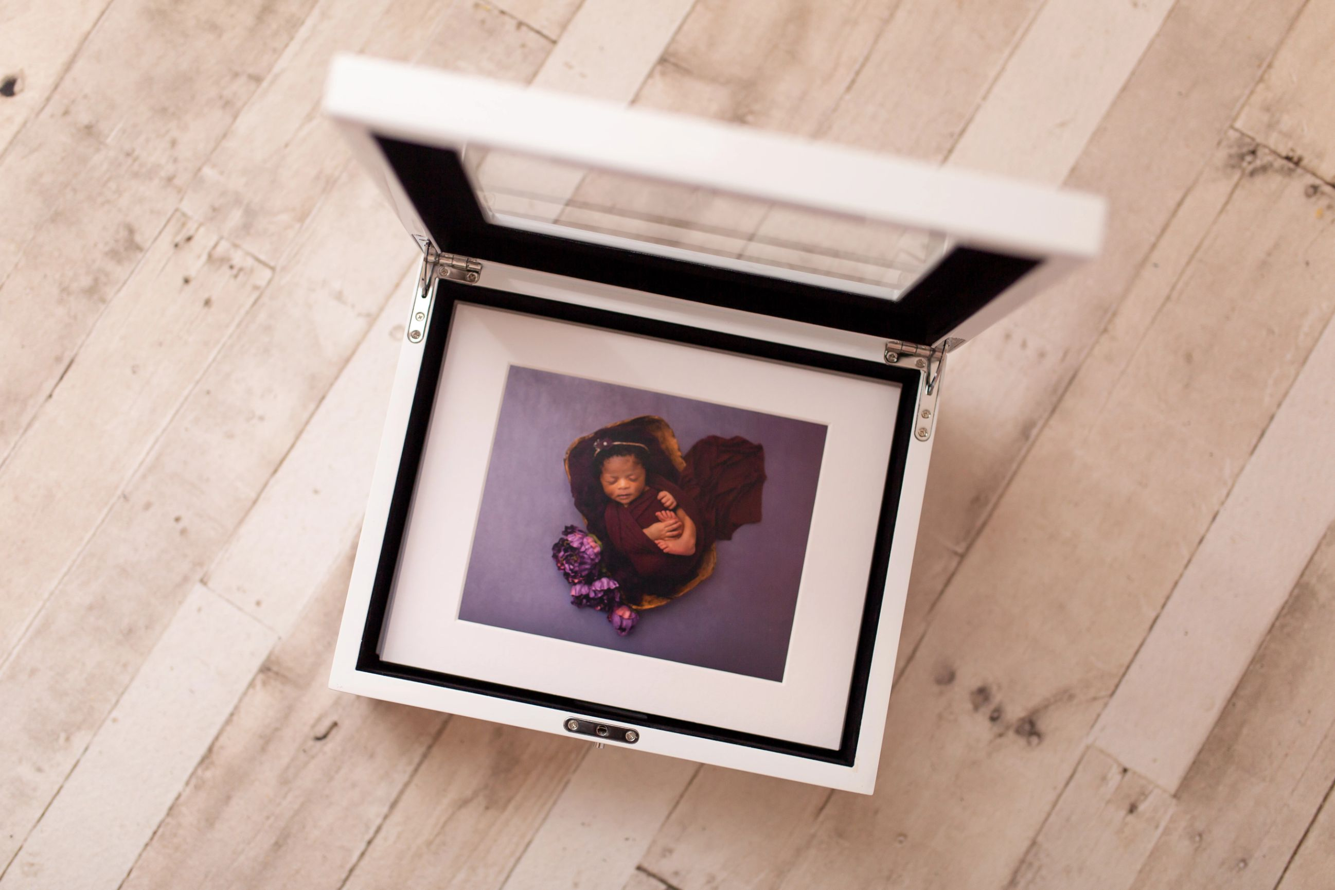 Award winning photograph of newborn in a crib with sibling displayed in a folio box