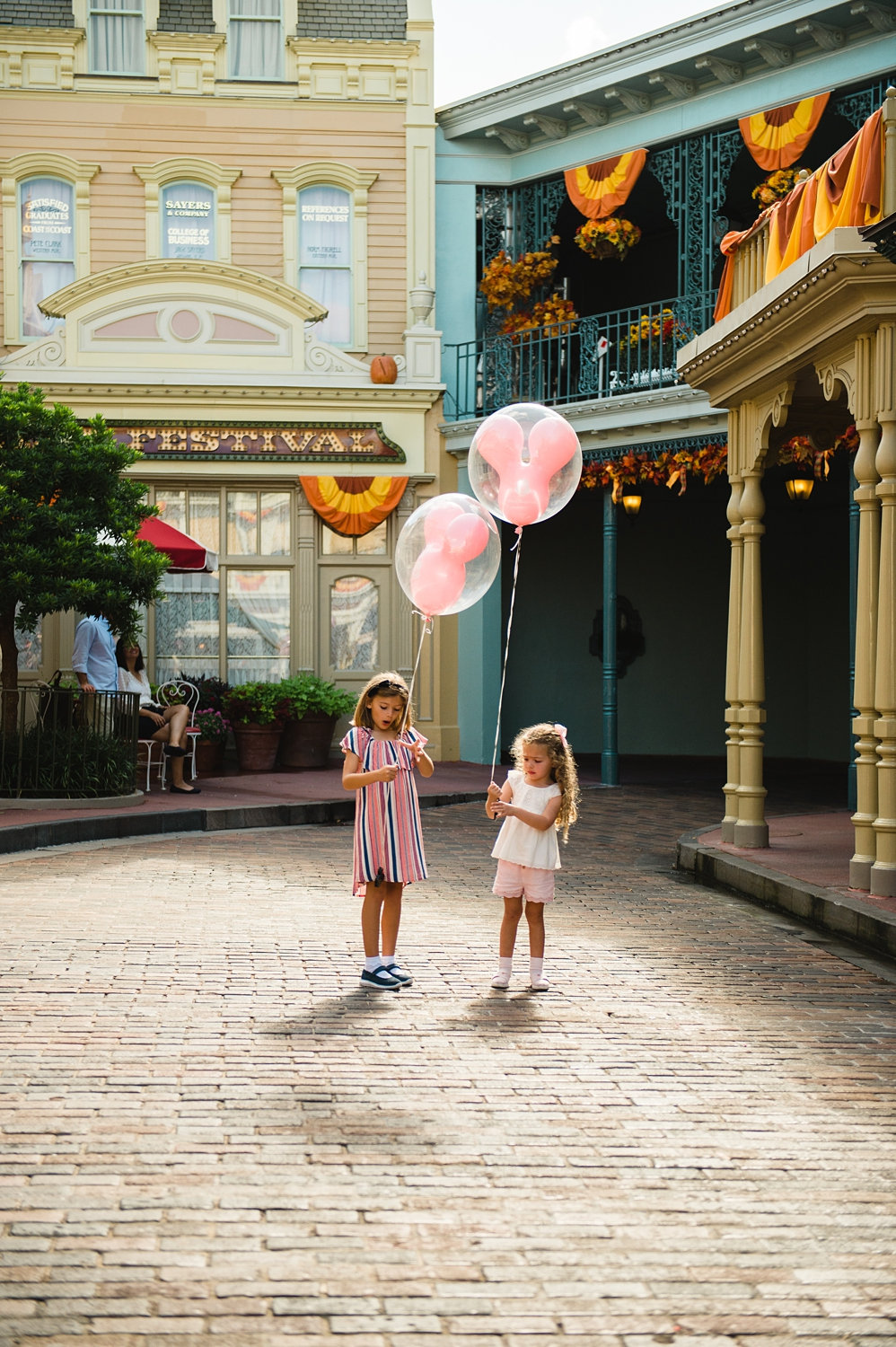 two girls with Mickey balloons, Main Street U.S.A. fall decorations, Ryaphotos