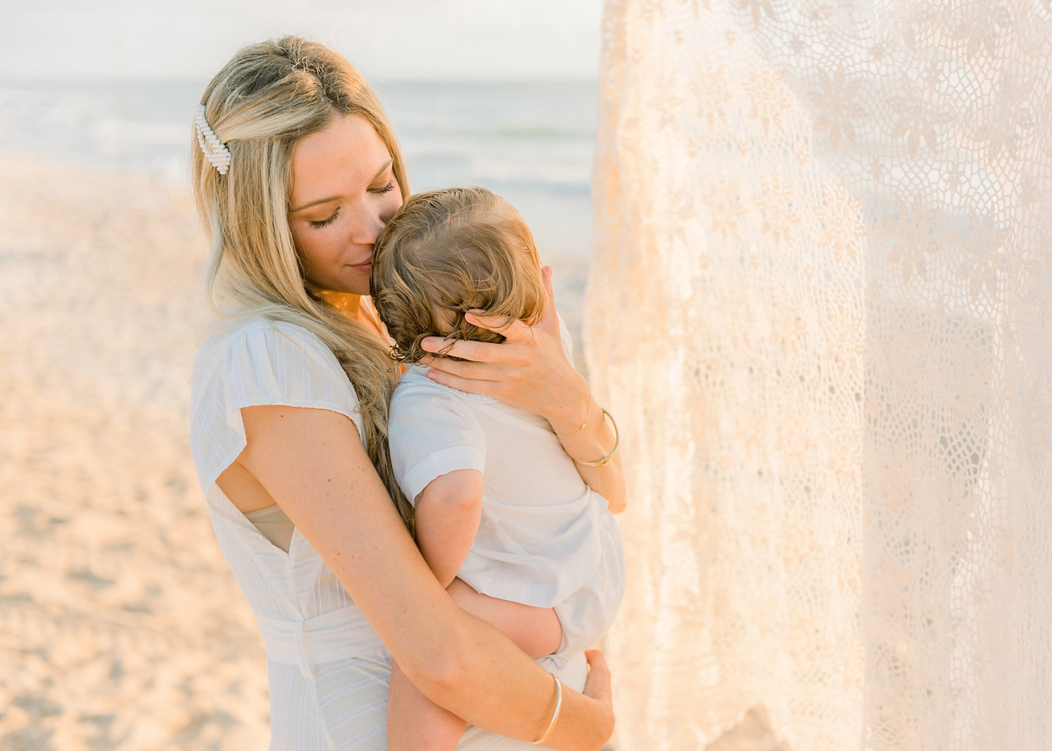 mother nuzzling her baby boy, eyelet curtain, coastal family portraiture