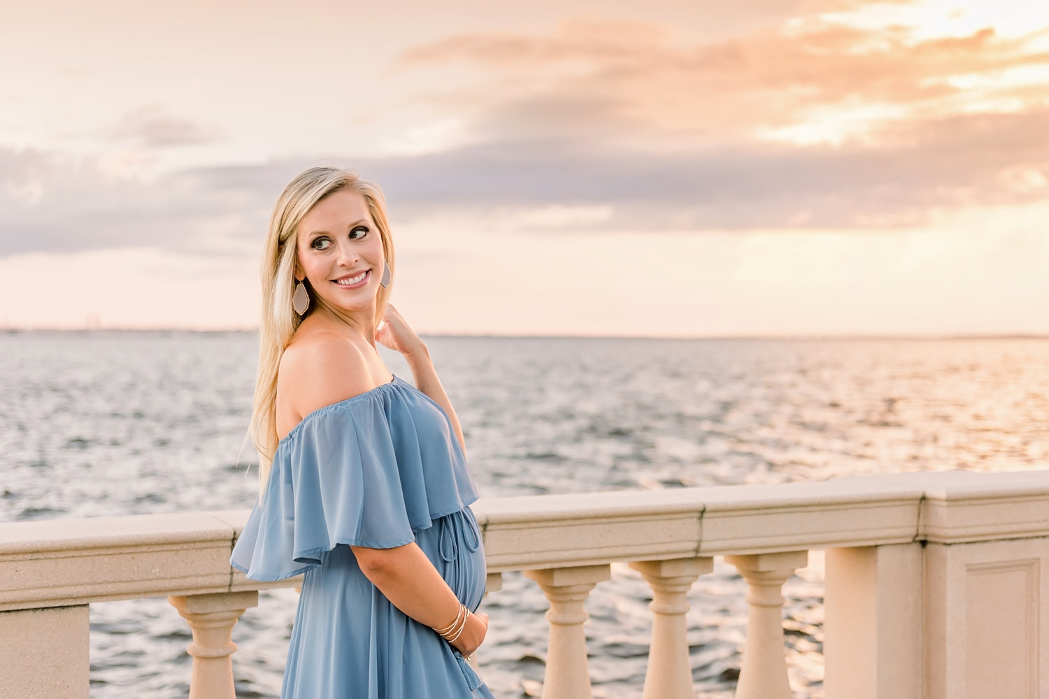 pregnant blonde woman smiling over her shoulder, old world architectural elements and the ocean behind her