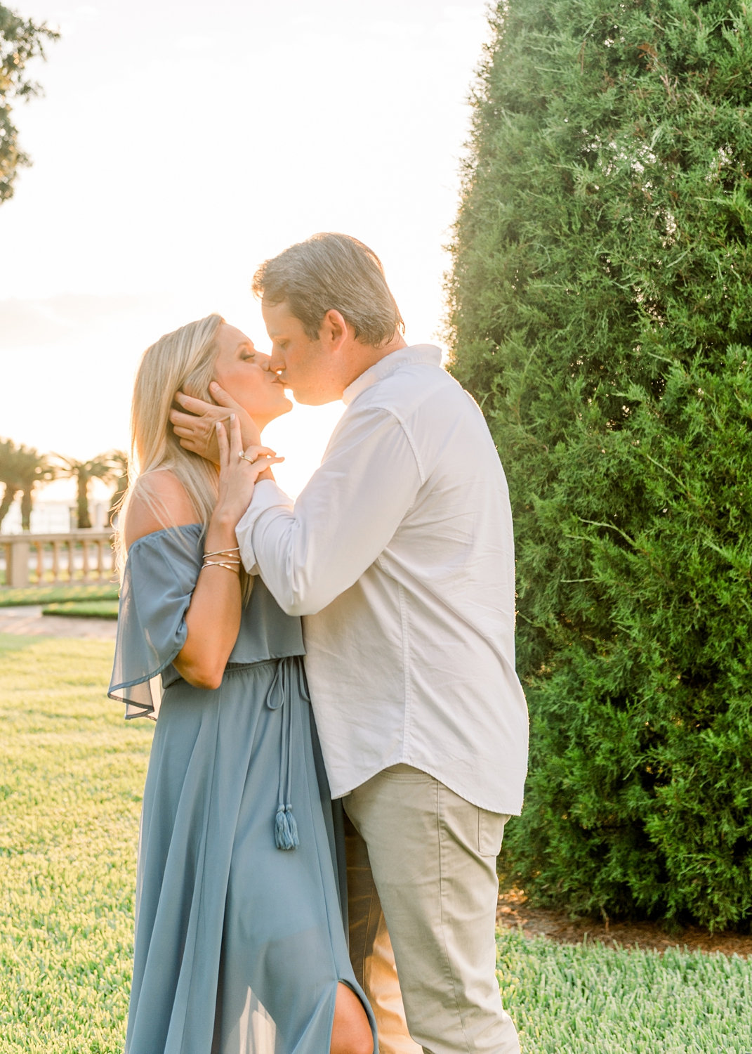 couple kissing in a manicured garden in Jacksonville, Florida, pregnant woman kissing her husband